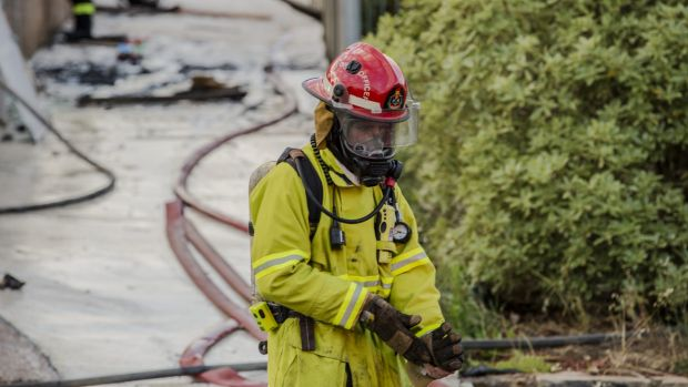 A firefighter on the scene of a house fire at Kinsella Street at Karabar on Friday.