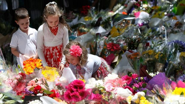 Sea of blooms: A girl adds flowers to the tributes at Martin Place.