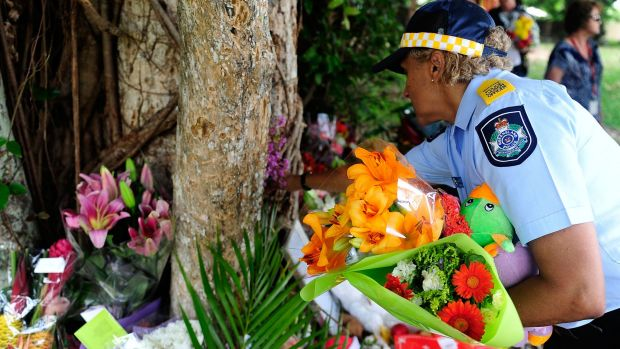 A police liason officer places flowers at a makeshift memorial in a park next to the home where eight children died in ...