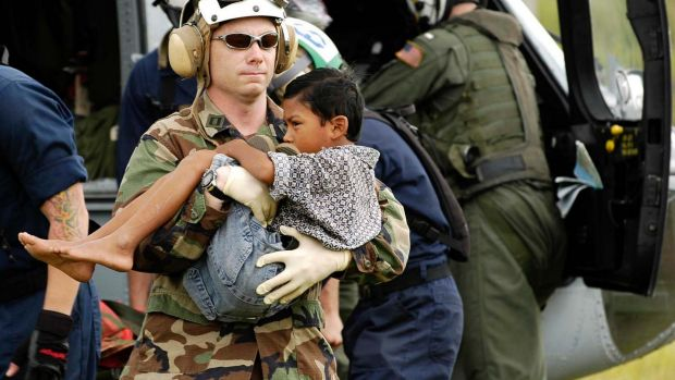 Lt. Shawn Harris carries an injured boy to a triage site setup by various relief groups on the Sultan Iskandar Muda Air ...