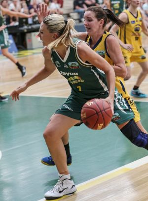 Turning back the clock: Dandenong's Penny Taylor drives forward against the Flames.
