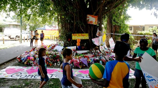 Children leave paintings and toys at a tree near the house in Cairns.