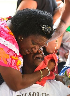 Grief-stricken: Family members mourn at the scene of a memorial in the park next to the home of seven of the eight ...