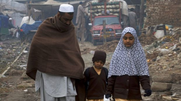 Cold comfort: A man walks his children home from school in the north-western city of Peshawar after the massacre.