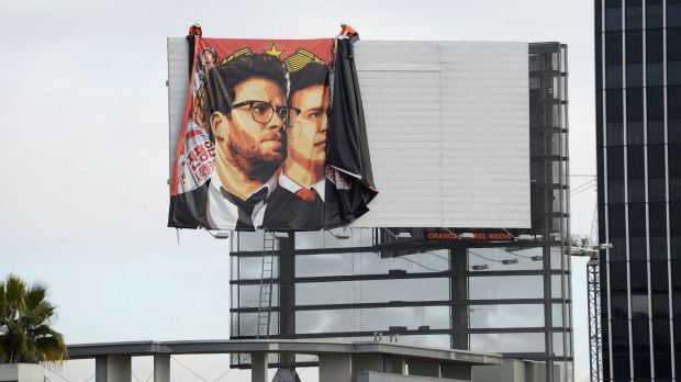 Workers remove a banner poster for <i>The Interview</i> from a Hollywood billboard.