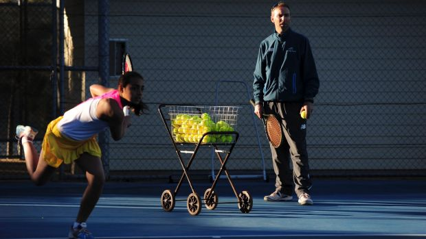Todd Larkham watches Annerly Poulos train at the AIS courts.