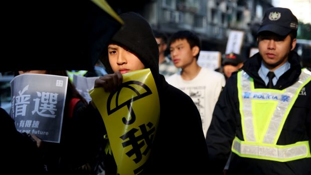 A protester holds a sign during a pro-democracy protest in Macau on Saturday.