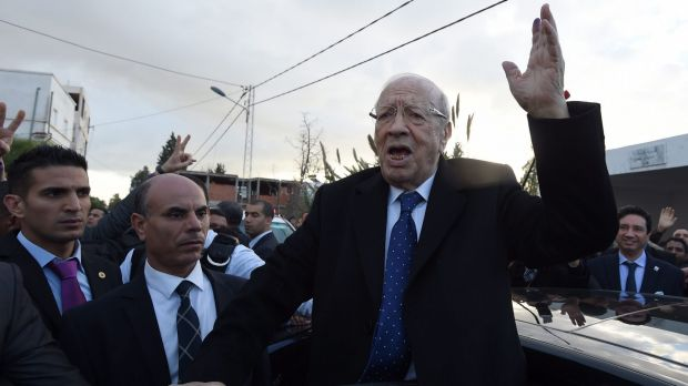 Frontrunner Beji Caid Essebsi waves to supporters after placing his vote on Sunday in Tunis.