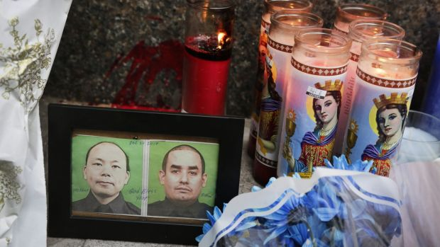 Photographs of slain police officers Wenjian Liu and Rafael Ramos are placed in a makeshift memorial in Brooklyn.