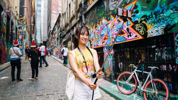 A tourists captures the moment in Hosier Lane using the popular Selfie Stick.