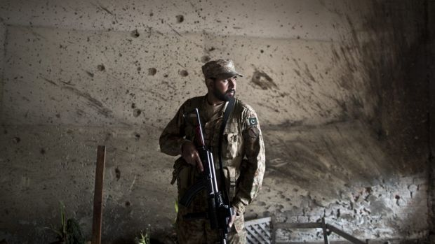 A Pakistani army officer stands guard inside the school in Peshawar that was attacked last week.