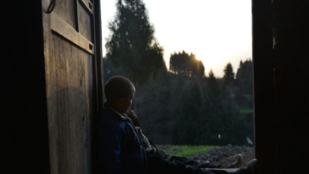An eight-year-old boy - who suffers from HIV and was given the pseudonym 'Kunkun' by Chinese media - sits on a doorsill ...