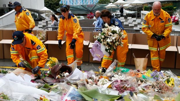 Volunteers from the Rural Fire Service removed flowers from the Martin Place memorial on December 23. The flowers will ...