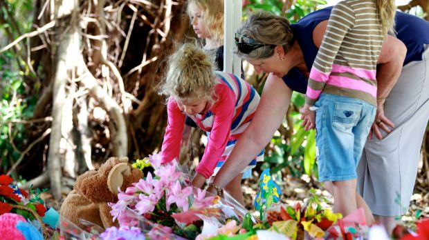 Mourners lay flowers at the memorial for eight children killed in Cairns.