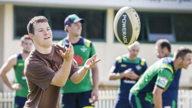 Branch Out Disability Services participant Tim Carr kicks the ball around with Canberra Raiders players at Raiders HQ.