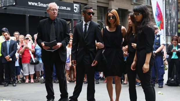 Siege survivors Joel Herat (second from left), Elly Chen (second from right) and Fiona Ma (right) pay their respects at ...