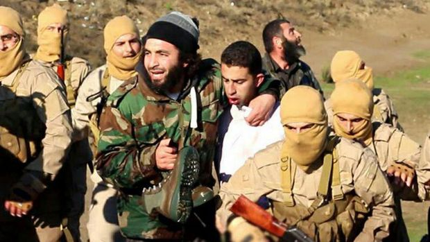 In an image released by Islamic State's Raqqa Media Centre, militants claim to have kidnapped Jordanian pilot (centre) ...