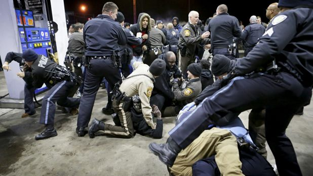 Police attempt to control an angry crowd at the scene of the shooting.