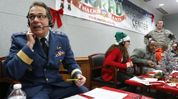 Canadian Brigadier General Guy Hamel, left, joins other volunteers taking phone calls from children around the world ...