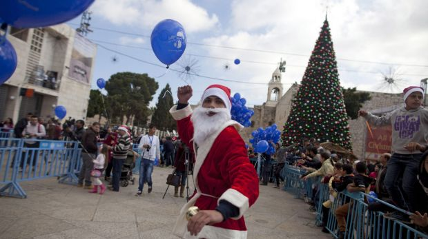 Santa dashes back to his sleigh outside the Church of the Nativity in Bethlehem, West Bank at the spot many pilgrims ...