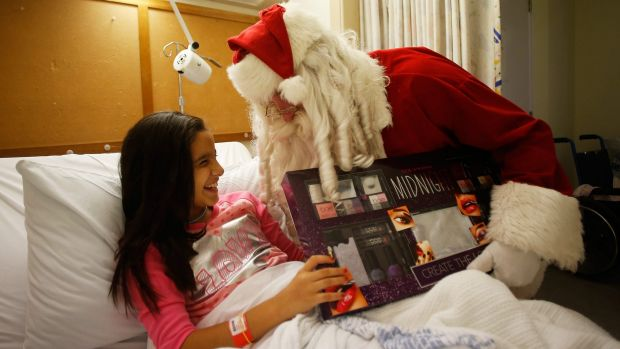 Zoe Labban receives a present from Santa on Christmas Day at Westmead Children's Hospital.