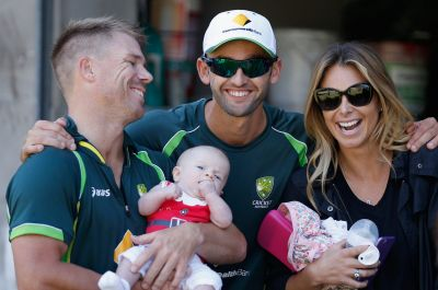 David Warner and partner Candice Falzon with their daughter pose for a photo with Nathan Lyon.
