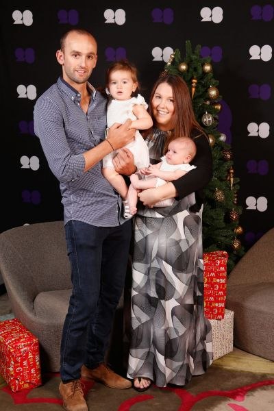 Nathan Lyon and his partner Mel Waring pose for a photo with their children Milla and Harper.