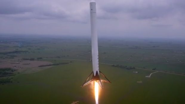 A screen grab from a video a drone shot showing a prototype reusable rocket launch and land itself.
