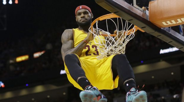 Star power: Cleveland Cavaliers forward LeBron James hangs onto the basket after a dunk.