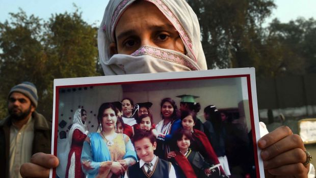 A Pakistani woman holds a photograph of her son, outside an army-run school in Peshawar after his death during the ...