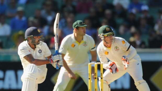 India opener Murali Vijay sweeps as Australia's Shane Watson (centre) look on late on day two of the Boxing Day Test.