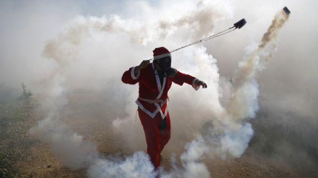 A Palestinian protester, dressed as Santa Claus, uses a slingshot to return a tear gas canister fired by Israeli troops ...