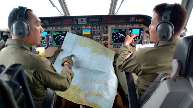 Pilot of navy airplane CN235 M. Naim holds a map to co-pilot Rahmad while flying over the Java sea during joint search ...