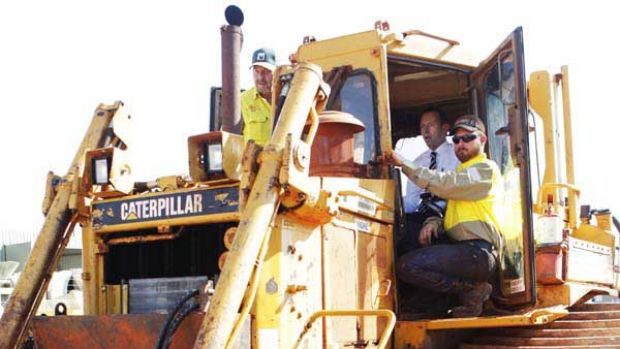 Tony Abbott sits behind the wheel of a bulldozer during a visit to McCoskers Contracting in Gladstone, Queensland.