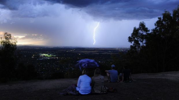 People gather at the top of Mt Ainslie as a lightning storm can be seen across Canberra in December.