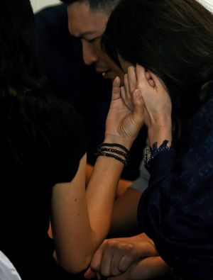 Distressed family members of passengers onboard the missing flight pray together.