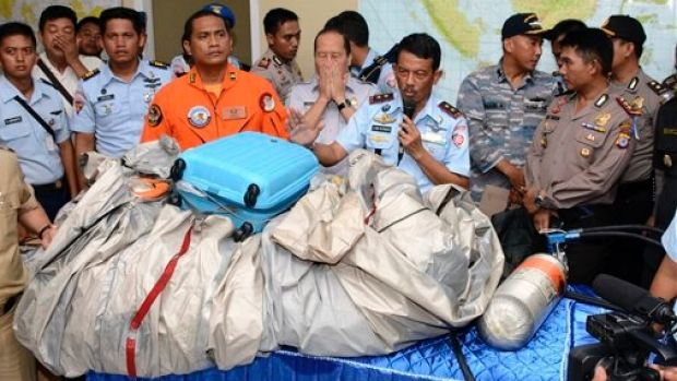 Airplane parts and a suitcase found floating on the water near the site where AirAsia flight 8501 disappeared.