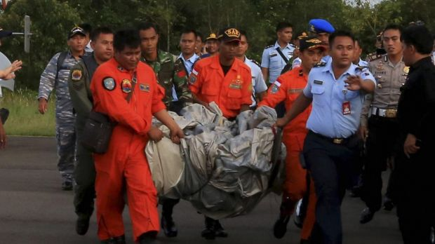 Rescue workers carry debris recovered from the ocean, presumed to be part of the AirAsia plane.