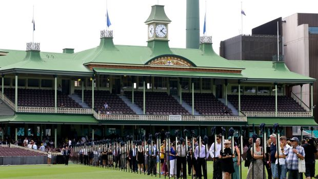 Tribute: Crowds observe 63 bats featuring images from Phillip Hughes' career prior to the memorial service for the ...
