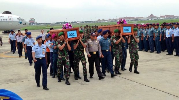 The first two bodies recovered from the AirAsia crash arrive at a military airport in Surabaya.