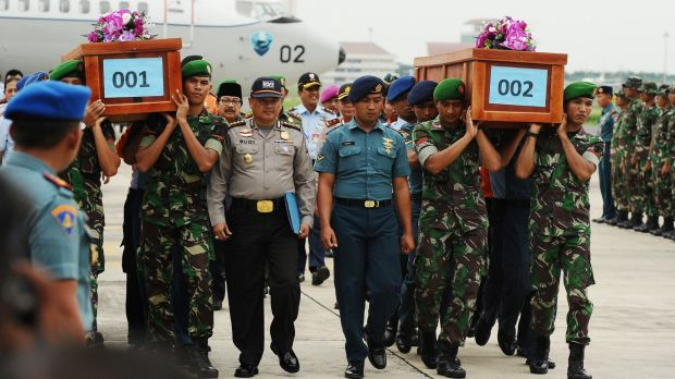 Indonesian soldiers carry coffins containing victims of the AirAsia crash at the Indonesian Air Force Military Base, ...
