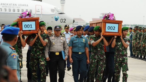 Indonesian soldiers carry coffins containing victims of the AirAsia flight QZ8501 crash at the Indonesian Air Force ...