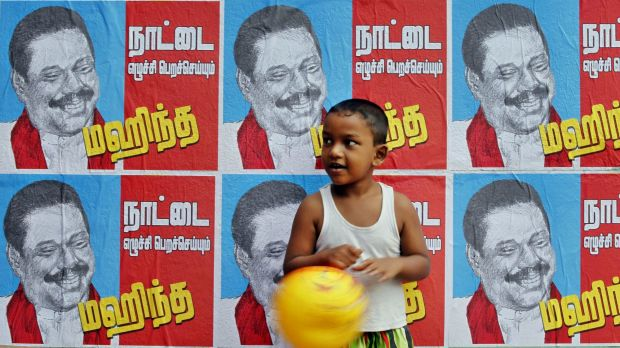 A Sri Lankan boy in Colombo stands next to a wall of election campaign posters spruiking Sri Lankan President Mahinda ...