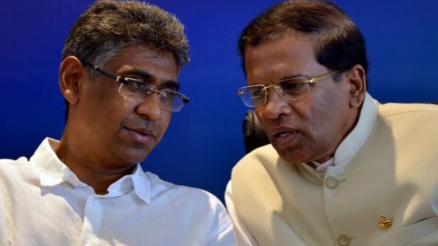 Sri Lanka's main opposition presidential candidate Maithripala Sirisena, right, listens to Investment Promotion Deputy ...