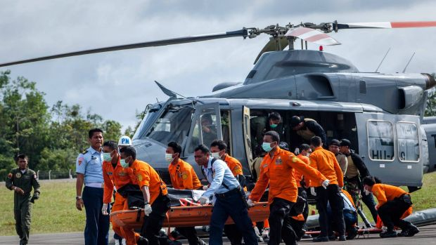 Members of Indonesian search and rescue team carry the body of a victim of the AirAsia flight QZ8501 crash at Iskandar ...