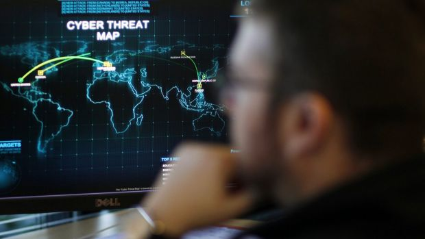 An information analyst works in front of a map tracking cyber threats.