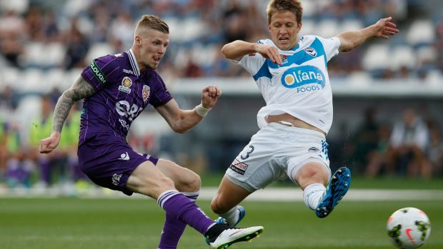 Andy Keogh of Perth Glory scores as Adrian Leijer of Melbourne Victory tries to defend in vain during the A-League match ...