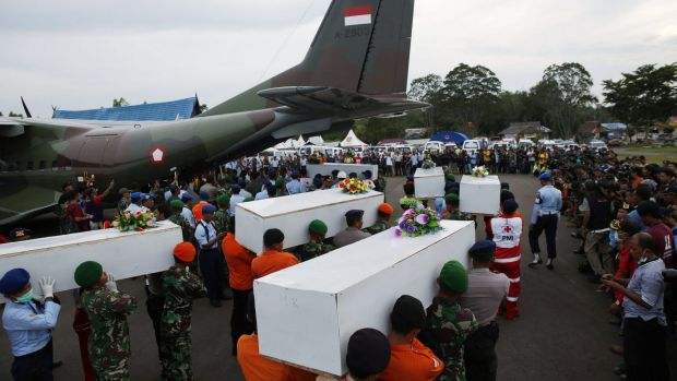 Bodies recovered from the sea are carried to a military transport plane to be taken to Surabaya.