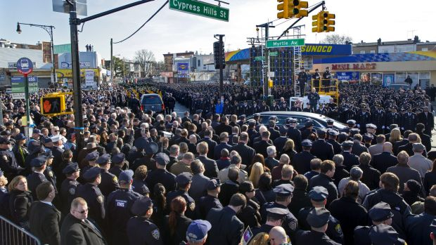 Thousands of police officers and others stand at attention as a hearse carrying New York City police officer Rafael ...