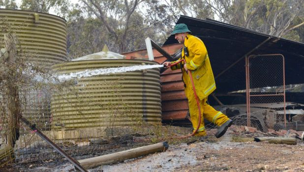 A Country Fire Service volunteer puts out spot fires next to a burnt out shed near One Tree Hill.